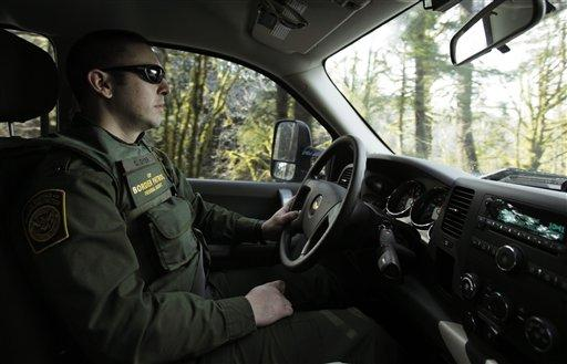 US Border Patrol Agent Chris Dyer drives his truck through a forested area near Forks, Wash., in March 2011.
