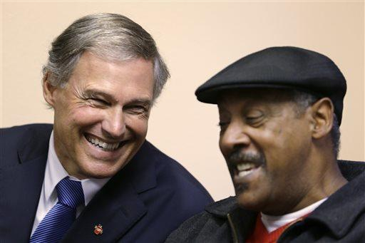 Gov. Jay Inslee shares a laugh with Charles Johnson as the two speak about having played high school football against each other decades earlier. Jackson is newly enrolled in Washington state's new health insurance exchange.