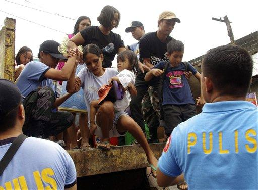 Residents living near the slopes of Mayon volcano are evacuated, Nov. 7, 2013,to public schools by police in anticipation of the powerful Typhoon Haiyan in central Philippines.