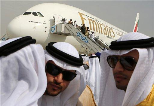 Emirati officials greet each other on Sunday in front of an Emirates Airbus A380 on display during the opening day of the Dubai Airshow in Dubai.