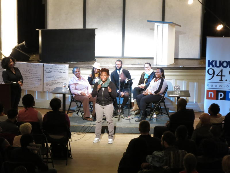 """The panel of guest speakers at """"Black In Seattle"""" listen as an audience member adds to the conversation."""