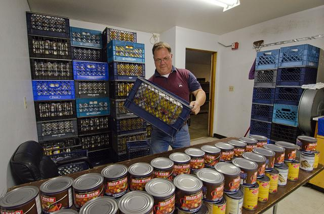 Tukwila Pantry Executive Director Joe Tice stocks the tables with canned goods in 2011.