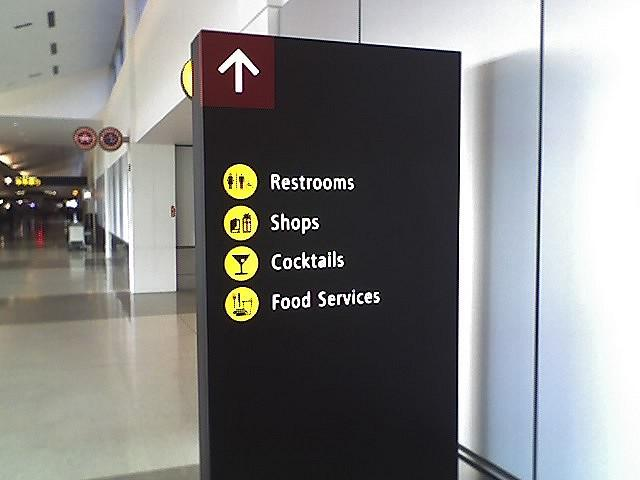 Signage in SeaTac aiport points towards shopping and food areas: lightning rods in the minimum wage debate.