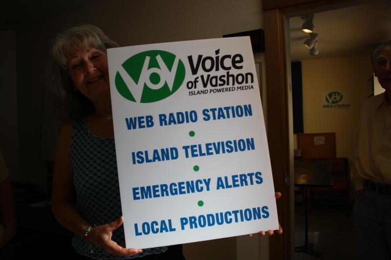 Susan McCabe with a sign advertising what Voice of Vashon offers to locals.