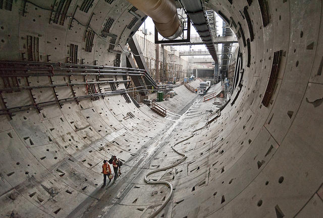 Two workers walk through the first rings of the tunnel toward Bertha, the SR 99 tunneling machine.