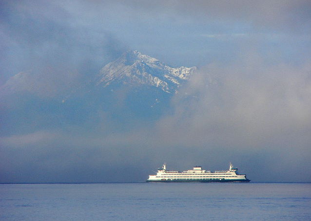 A ferry navigates through light fog on Puget Sound against the backdrop of the Olympics.