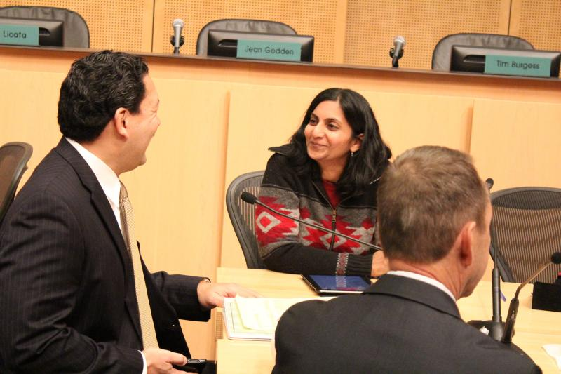 Socialist City Councilmember Kshama Sawant jokes with City Councilmember Bruce Harrell at her first City Council meeting.