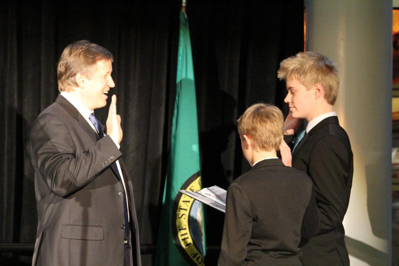 Newly re-elected City Councilmember Mike O'Brien is administered the oath of office by his sons Elliott and Wyatt.