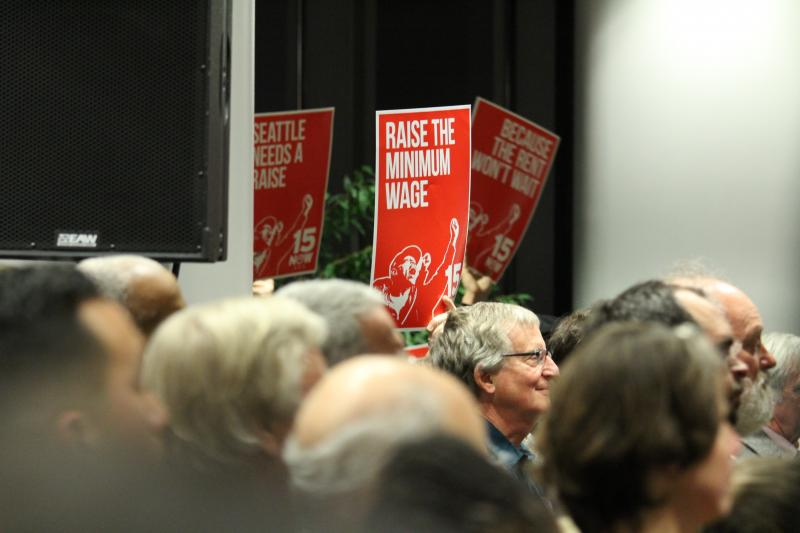 At Monday's inauguration, many people held signs supporting the $15 an hour minimum wage in Seattle.