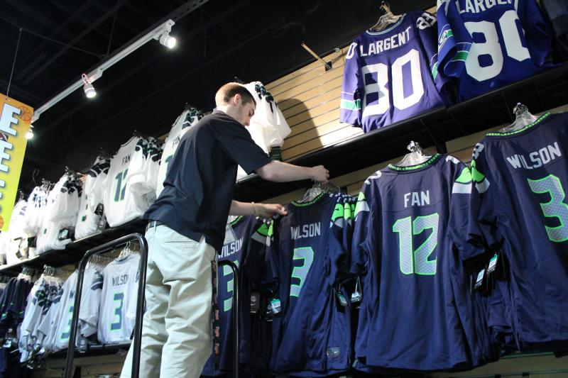 "Tom McMaster, of Just Sports in Alderwood Mall, hangs more ""12th Man"" uniforms. The success of the team has made them hot commodities."
