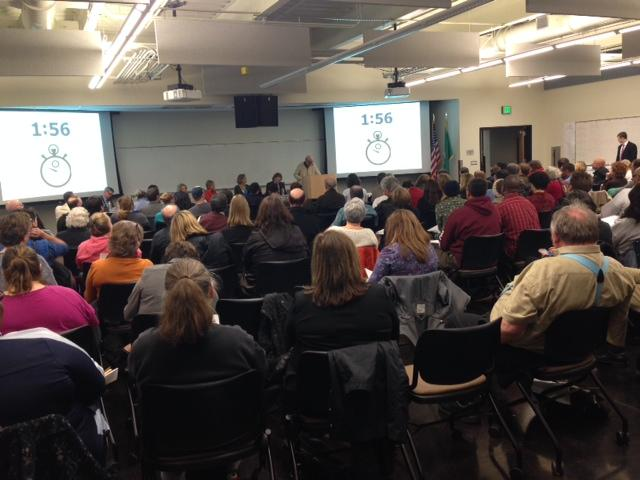 Parents in a packed room listen to public testimony regarding proposed charter schools in the Seattle area at South Seattle Community College on Monday.