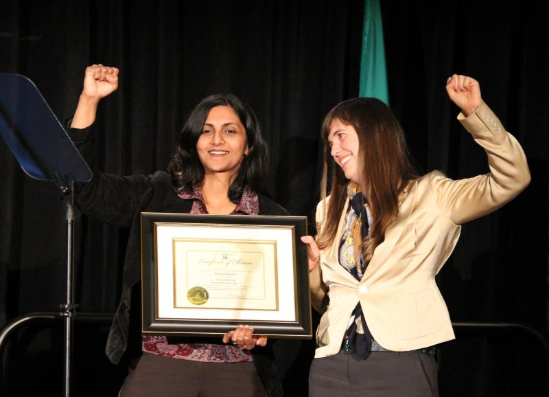 Newly-elected Socialist City Councilmember Kshama Sawant celebrates her inauguration with a raised fist. She was sworn in by Nicole Grant of the Washington State Labor Council.