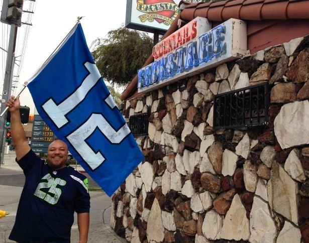 Cedric James Morris, founder of the Los Angeles Seahawks fan group, stands outside Backstage, in Culver City. The bar has become so overrun with Seahawks fans on Sundays that Morris has a list of overflow bars he hands out to fans when Backstage fills up.