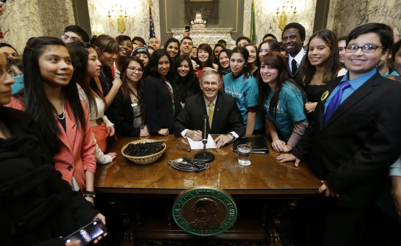 Washington Gov. Jay Inslee, center, poses for a photo with a group of students, after he signed into law a measure that expands state financial aid to students living illegally in the country, Wednesday, Feb. 26, 2014, at the Capitol in Olympia, Wash.