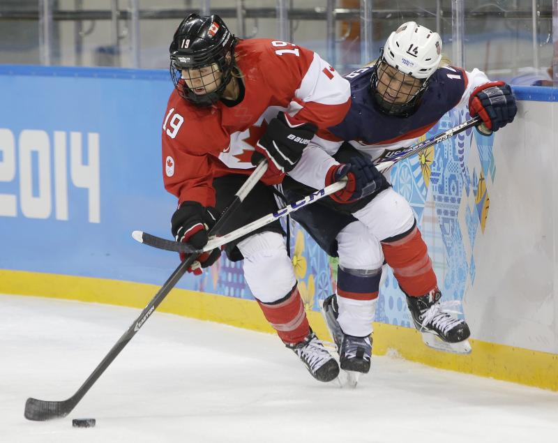 Brianne Jenner of Canada and Brianna Decker of the United States battle for control of the puck during the second period of the 2014 Winter Olympics women's ice hockey game on February 12, 2014, in Sochi, Russia.