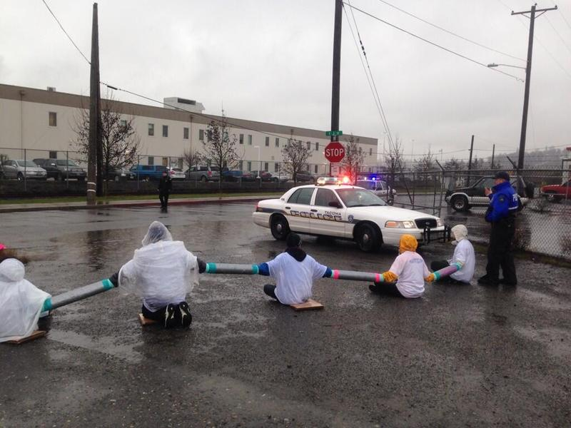 A dozen protesters block the entrance to the Northwest Detention Center in Tacoma in February 2014. Deportations from the Northwest have declined by nearly half, but now a larger proportion of deportees have a clean record.