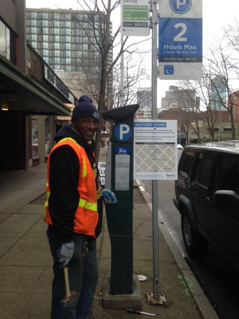A city  worker used a mallet to bang in signs next to the new meters soliciting feedback from parking patrons about the new meters.