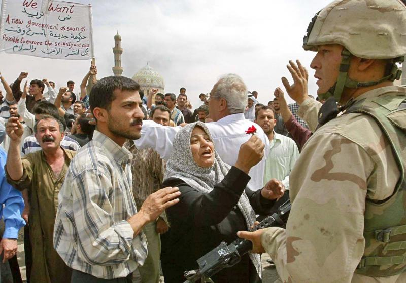 An Iraqi woman offers a flower to an American Army soldier in the center of Baghdad, as hundreds of Iraqi demonstrate demanding peace and security, Saturday, April 12, 2003.
