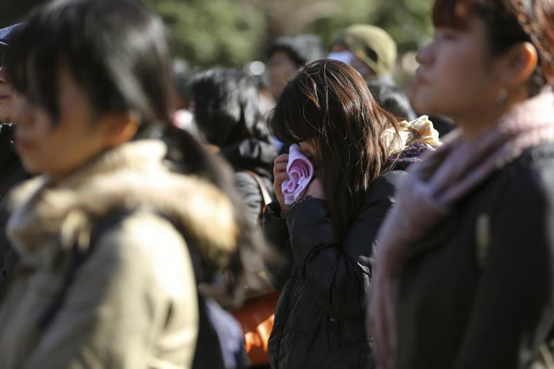 People mourn for victims of the March 11, 2011 earthquake and tsunami, in Tokyo, Tuesday, March 11, 2014.