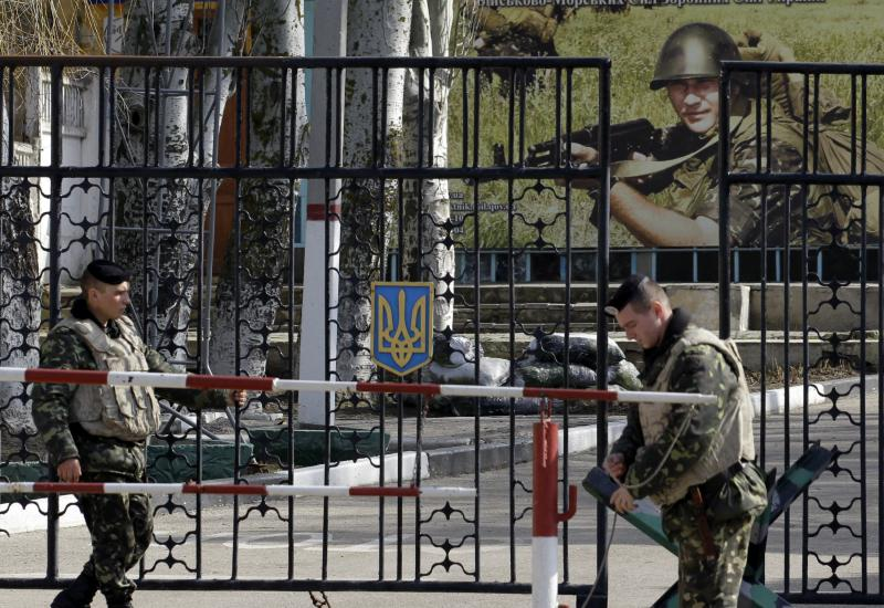 Ukrainian soldiers stand guard at the gate of a military base in the port of Kerch, Ukraine, Monday, March 3, 2014.