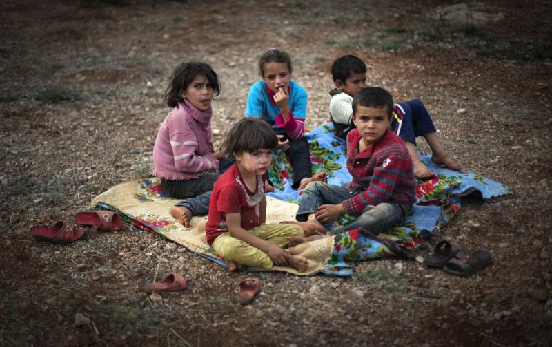 Syrian children who fled with their families from the violence in their village, sit on the ground at a displaced camp in the Syrian village of Atmeh, near the Turkish border with Syria, Thursday, Nov. 8, 2012.