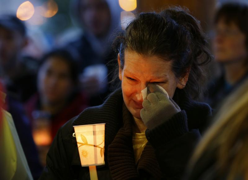 Teresa Welter cries as she holds a candle at Tuesday's candlelight vigil in Arlington, Wash.