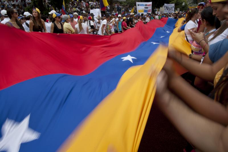 Demonstrators wave a Venezuelan flag during an anti-government protest in Caracas, Venezuela, Sunday, March 2, 2014.