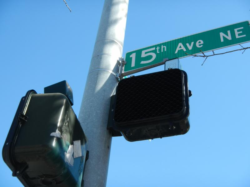 The small speakers at certain intersections in Seattle emit a tone to signal when it is safe to cross for the blind or visually impaired.