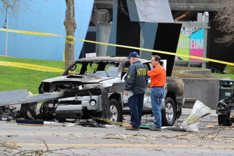 Officials examine one of the three cars damaged in the crash.