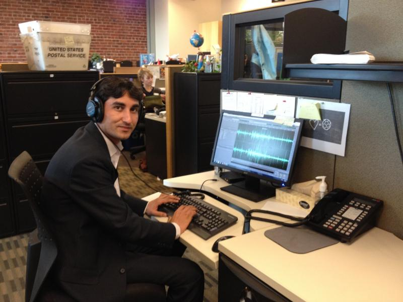 Visiting journalist Naveed Alam at his desk in the KUOW newsroom