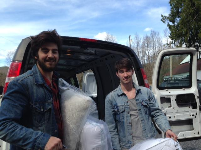 Chris Pavlik and Cody Mortensen unload donated bedding near the Oso Chapel.