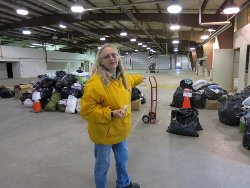 Shirley Clark surveys the hangar at the Arlington airport where goods for Oso relief have been collected. With donations piling up, she has been walking about with a half-eaten sandwich and trying to keep organized.