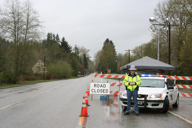 A State Patrol post blocks cars from traveling west on state Route 530 out of Darrington, Wash.