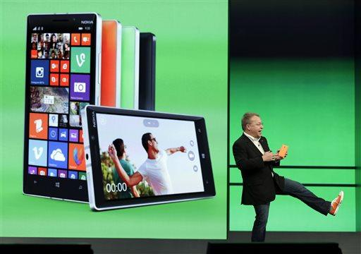 Stephen Elop, executive vice president of Nokia shows off his colored shoe while talking about the colors available of the new Nokia Lumia 930 phones during a keynote address at the Microsoft Build Conference Wednesday, April 2, 2014.