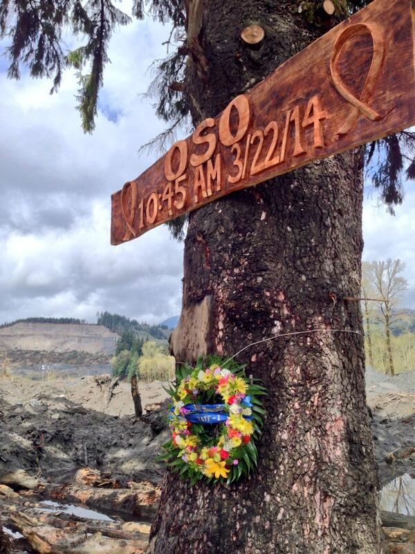 A memorial for victims hanging on a tree on the mudslide debris pile.