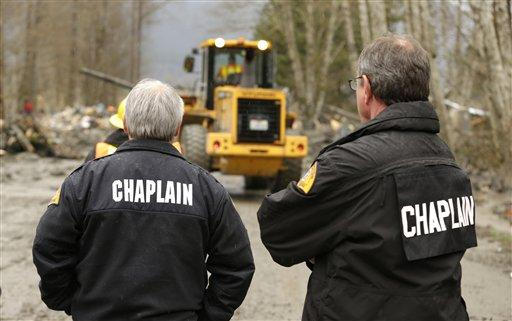 Washington State Patrol chaplain Mike Neil, right, looks on with a colleague as workers using heavy equipment work to clear debris from the Oso mudslide.