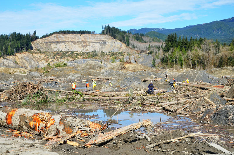 In this photo from April, rescue workers search in the debris of the Oso mudslide. At its peak, there were over 900 people on the pile, but efforts have been scaled down.