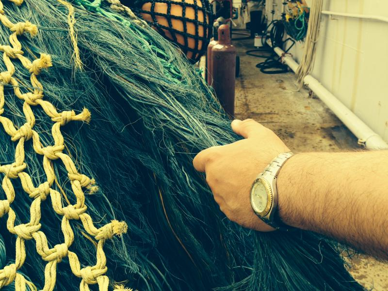 Alan Davis shows chafing gear, a nylon material that prevents wear on fishing nets as they are pulled onto a ship