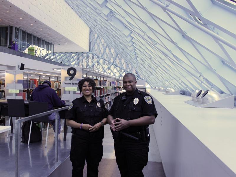 Yolanda Cooper (left, employed 1 1/2 years) and Warner Adoga (employed 3 months). Guards at the library keep the library safe by making sure patrons follow the rules; mostly by waking up patrons who drift off in the chairs.