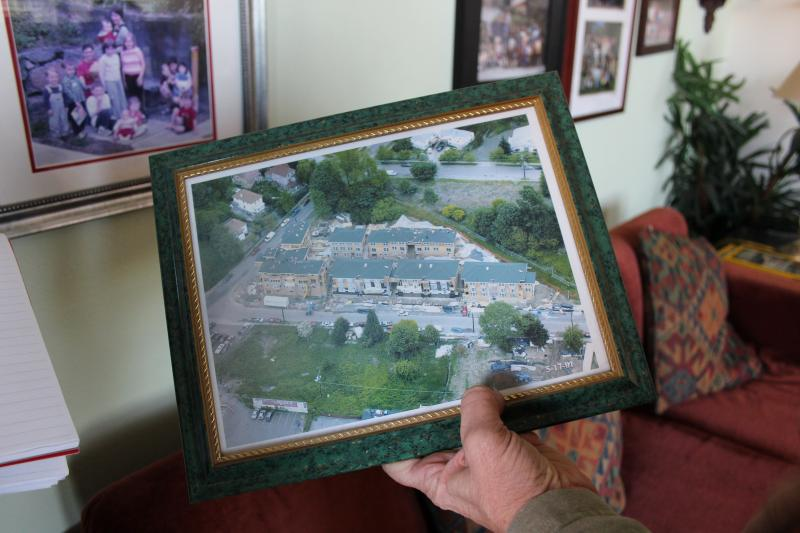 Susan Stafford holds a photo of Jackson Place Cohousing.