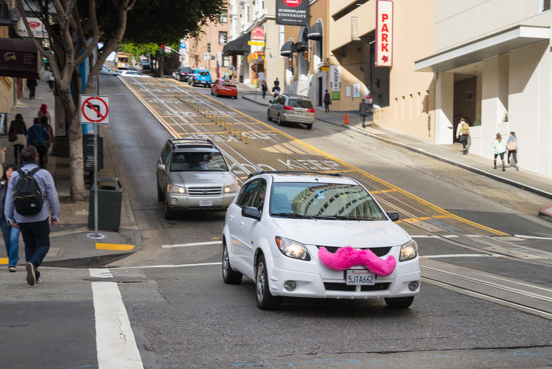 A Lyft for-hire car rolls down a street in San Francisco.