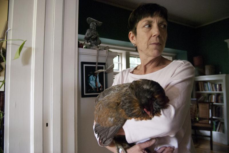 Paulette Hopke of Wild Old Women (And One Young Man) House holds an ailing chicken.