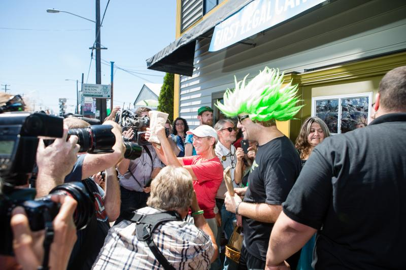 Deb Green, the first person to purchase legal recreational marijuana at Cannabis City, holds up her bag while exiting the store as colorfully-coiffed Jeremy Cooper looks on.