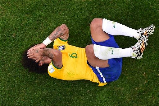 Brazil's Marcelo lies on the pitch during the World Cup semifinal soccer match on Tuesday. The host country was routed by Germany 7-1.