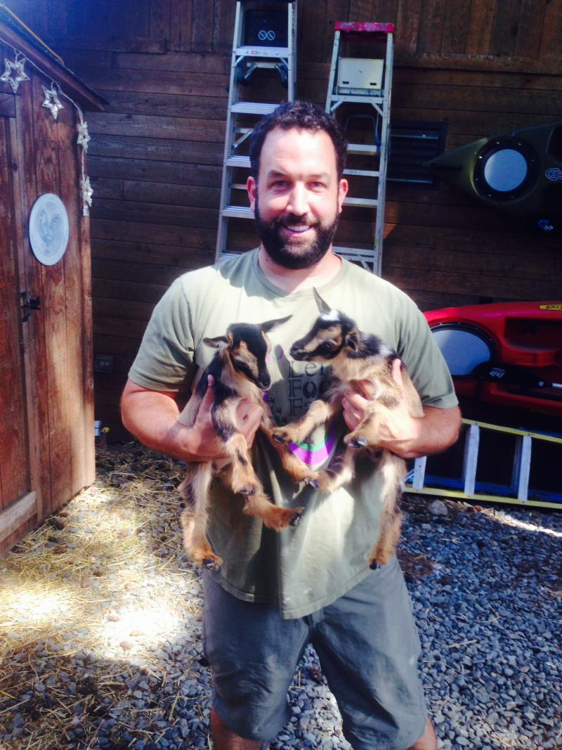 Left Foot Farm owner Jeremy Foust hold two baby Nigerian dwarf goats.