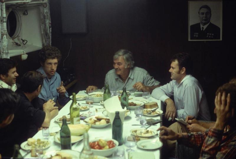 "Soviet and US fishermen meet in the evening in the galley of a Soviet ship. Tony Allison, left, interprets (1979): ""I think the silver-haired guy on my immediate left, fisherman Barry Fisher had just told an off-color joke."" On the wall: Leonid Brezhnev."