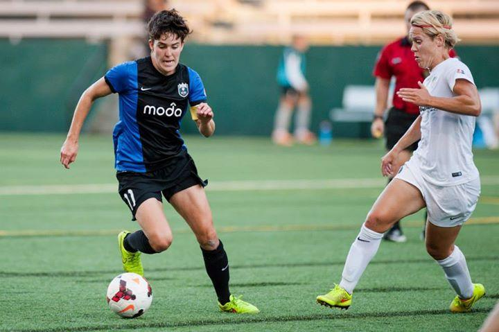 Seattle Reign FC captain Keelin Winters dribbles around Washington Spirit's Lori Lindsey at Memorial Stadium in downtown Seattle.