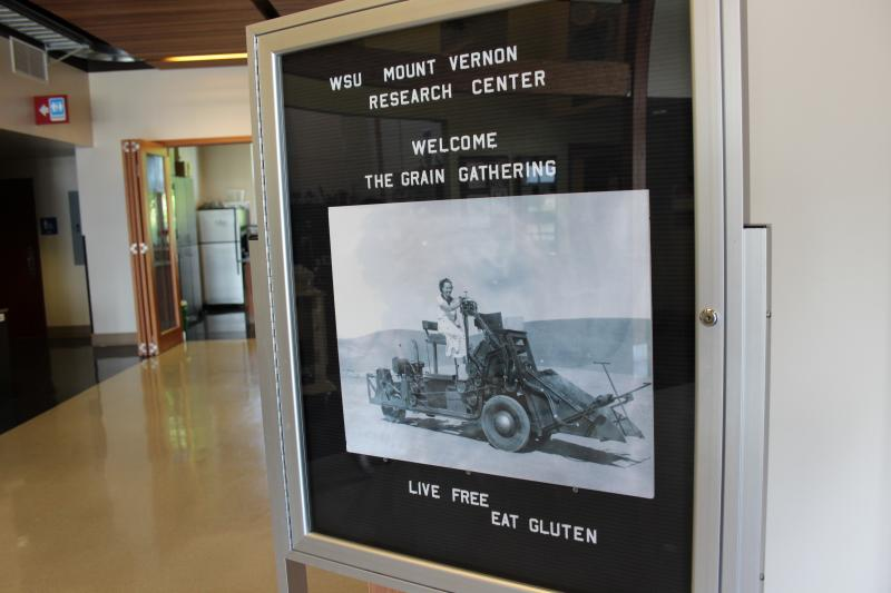 "A sign outside the main auditorium for the Grain Gathering encourages participants to ""Live free, eat gluten."""