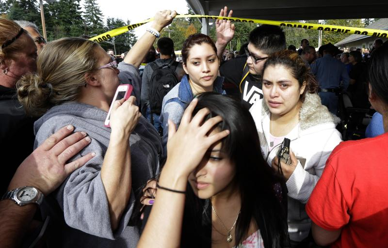 Parents and students move under police tape at a church on Friday where students were taken following a shooting at Marysville Pilchuck High School in Marysville, Wash.