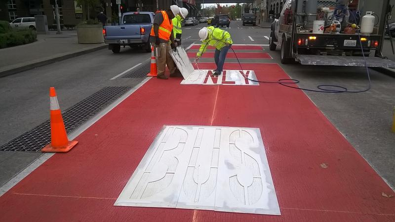 An SDOT Crew puts the finishing touches on a bus-only lane on Battery Street in Seattle's Belltown Neighborhood.
